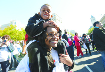 Joshua Ingram, 6, and Terrelle Ingram, 29, enjoy the remainder of the afternoon in front of Freedom Plaza in Northwest Washington after participating in the 27th Annual AIDS Walk on Saturday, Oct. 26.