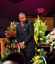 Sheila Stewart's driver Darnell Lee stands by her coffin in a final moment together with his friend at the funeral service for Stewart at University Park Baptist Church in Charlotte, N.C., on Oct. 30. Stewart, a longtime radio personality in D.C., was killed Oct. 24 in an automobile accident in Atlanta. (Paul Williams/Paul-3 Photography)