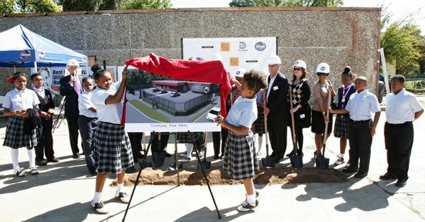 Two St. Philip's School children unveil the design of the St. Philip's School and Community Center food pantry, Oct. 17.