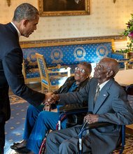 President Barack Obama greets Richard Overton, with Earlene Love-Karo, in the Blue Room of the White House, Nov. 11, 2013. Mr. Overton,107 years old and the oldest living World War II veteran, attended the Veteran's Day Breakfast at the White House.
