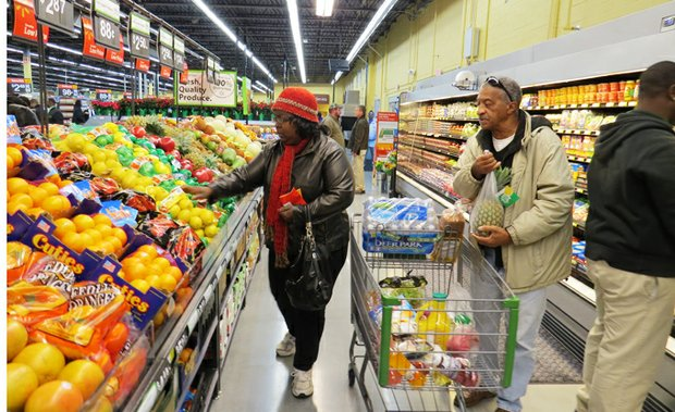 Arinthia and Cleo Rackley, who live in the Hidden Hills subdivision, load up their shopping cart with fresh fruit and vegetables at the new Walmart Neighborhood Market in the Covington Square Shopping Center in Lithonia.