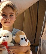A child holds stuffed toy animals distributed by the International Rescue Committee.
