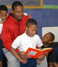 Baltimore Ravens tight end Ed Dickson reads to children at the Webster Kendrick Boys & Girls Club in Park Heights on Tuesday, November 12, 2013. (Left to right) Edward Tillery; James Morris (shoulder); Dikias White (Reading); Antuane West; Kareem Moore; and Brian Crawford.