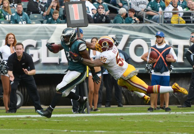 Philadelphia Eagles running back LeSean McCoy is tackled by Washington Redskins inside linebacker Perry Riley. McCoy earned the NFL's rushing record during the game.