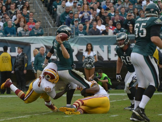 Washington Redskins outside linebacker Brian Orakpo and defensive end  Jarvis Jenkins wrap Philadelphia quarterback Nick Foles for a sack.