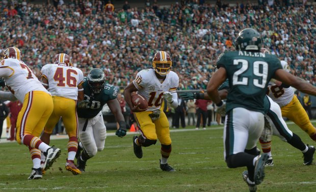 Washington Redskins quarterback Roberts Griffin, III splits through Eagles defenders for a short gain in the 2nd quarter. After 4th quarter comeback attempt the Redskins fell to the Eagles 16-24.