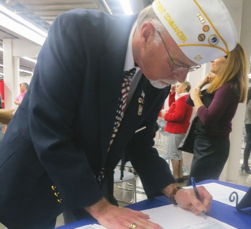 Commander Mike Morris of the Oregon American Legion Post 21 signs the Community Covenant Thursday, Nov. 14 at Veterans Memorial Coliseum.