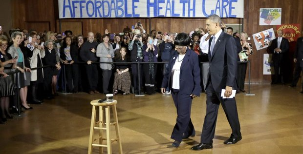 President Barack Obama walks in with ACA volunteer Edna Pemberton before speaking with other volunteers who helped people enroll through the HealthCare.gov site at Temple Emanu-El, a Dallas Area Interfaith, Nov. 6. Obama traveled to Dallas and other cities in Texas to discuss health care and raise money for the Democratic party.
