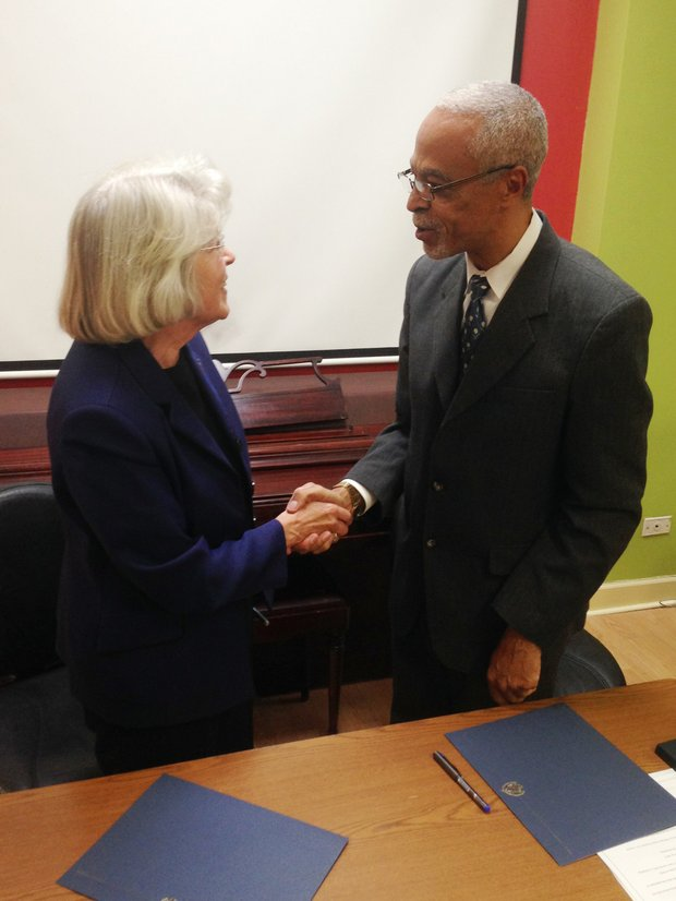 Dr. Sharon K. Hahs, President, Northeastern Illinois University and A. Patrick Augustin, Executive Director, Pan-African Association shake hands after establishing an official partnership between their respective organizations.