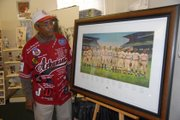 Ray Banks with a donated painting of Negro League baseball players