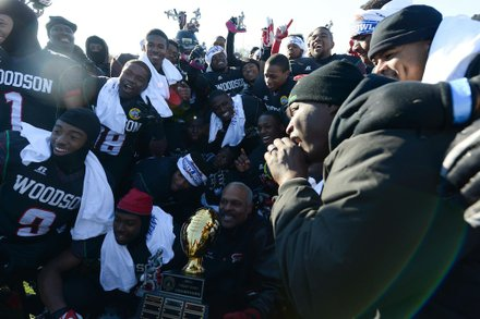 Former H.D. Woodson football head coach Gregg Fuller (center) poses with the team after it defeated Wilson High, 25-13, in the 44th Annual Turkey Bowl, a Thanksgiving tradition, in Southeast on Thursday, Nov. 28.