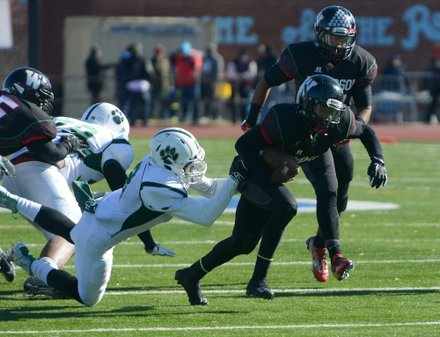 H.D. Woodson quarterback Rashad Cooper tries to break a tackle in the first quarter during the 44th Annual Turkey Bowl, a Thanksgiving tradition, in Southeast on Thursday, Nov. 28. H.D. Woodson defeated Wilson, 25-13.