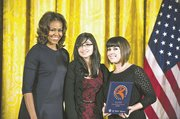 Project AIM representatives Miranda Luna (center) and Andrea Gates-Ingle (right) accept the 2013 National Arts and Humanities Youth Program Award from first lady Michelle Obama.