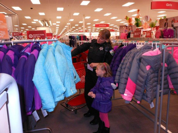 Officer Danielle Malone helps Rylee, 7, shop for a new winter coat.
