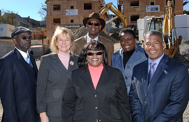 Gathered at the Quincy Heights development on Quincy Street in Dorchester are (l-r) John Strodder, general manager of United Housing Management, Jeanne Dubois, executive director of the Dorchester Bay Economic Development Corporation, Otis Gates, UHM chief financial officer, Patricia Farr, UHM director of human resources, Kevin Bynoe, UHM senior portfolio manager; (foreground) Sheila Harper, UHM director of compliance and training.