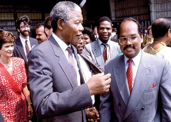 Nelson Mandela pauses to chat with City Councilor Charles Yancey during his arrival at Logan Airport in 1990.