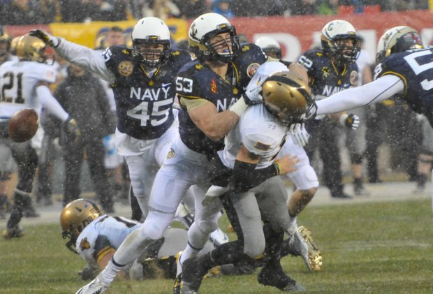 Navy Midshipmen linebacker Cody Peterson pressures Army Black Knights quarterback A.J. Schurr into a fumble during the first quarter of Navy's 34-7 win at Lincoln Financial Field in Philadelphia on Saturday, Dec. 14.