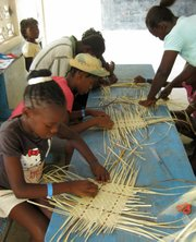 Children in Haiti learn to weave with instruction from two Making Roots youth workers. The two youth workers spent a week learning weaving skills and taught four weeks of workshops to children.