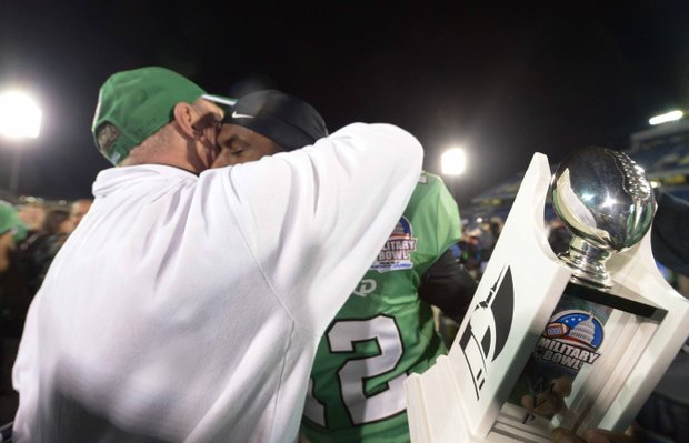 Marshall head coach Doc Holliday hugs quarterback Rakeem Cato after the 2013 Military Bowl on Friday, Dec. 27 at Jack Stephens Field at Navy-Marine Corps Memorial Stadium in Annapolis. The Marshall Thundering Herd defeated the Maryland Terrapins, 31-20.