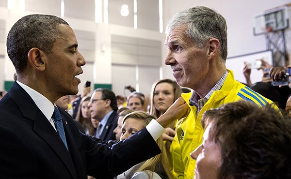 President Barack Obama talks with Tom Grilk, head of the Boston Athletic Association, as he greets first responders and marathon volunteers at Cathedral High School in Boston, Mass., April 18, 2013. The President and First Lady Michelle Obama traveled to Boston to attend an interfaith prayer service dedicated to the victims of the Boston Marathon bombings.