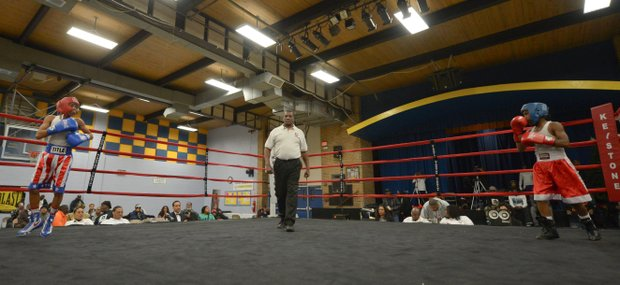 Kesean Bagwell (left) and Lawrence Malcolm stand in their respective corners as referee Keith Jones readies to start the second round of a three-round amateur bout at the District Heights Classic, an annual amateur boxing event, at the District Heights Municipal Center on Saturday, Jan. 4. Bagwell won the fight by decision.