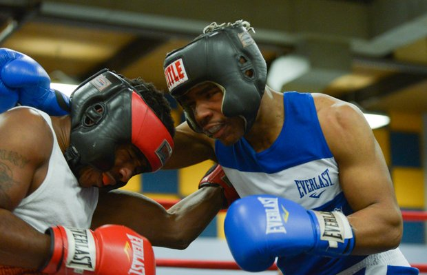 Davon Boone (left) tries to fight his way off the ropes against Gary Jones in the first round of their boxing match at the District Heights Classic, an annual amateur boxing event, at the District Heights Municipal Center on Saturday, Jan. 4. Boone won the match by decision.