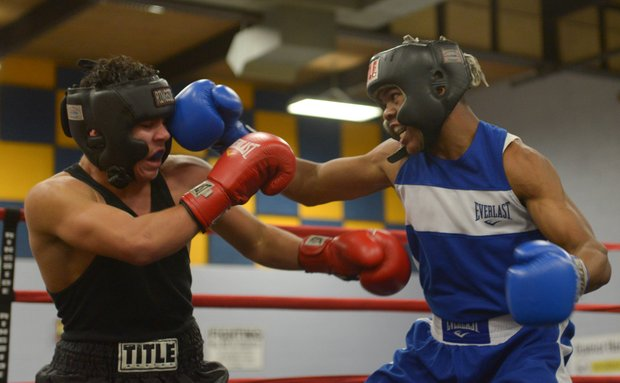 Gary Antwon Russell (right) lands a right hook against Tommy Avezar in the first round of their boxing match at the District Heights Classic, an annual amateur boxing event, at the District Heights Municipal Center on Saturday, Jan. 4. Russell won the match by decision.