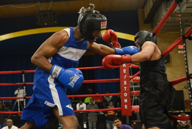Gary Antwon Russell (left) lands a punch against Tommy Avezar in the third round of their boxing match at the District Heights Classic, an annual amateur boxing event, at the District Heights Municipal Center on Saturday, Jan. 4. Russell won the match by decision.
