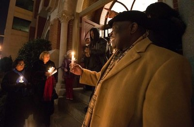 Pastor Lennox Abrigo leads a prayer during a candlelight vigil outside the Metropolitan A.M.E. Church in Northwest D.C. after the National Action Network-sponsored National Youth Day of Action Against Gun Violence summit on Wednesday, Jan. 8.