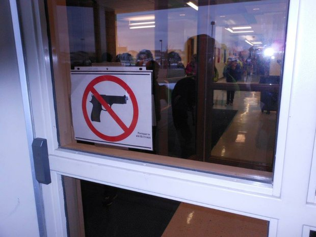 A sign designates Charles Reed Elementary School as a gun free zone where conceal carry permit holders will not be allowed to carry their side arms.