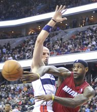 Miami Heat forward LeBron James passes around Washington Wizards center Marcin Gortat at Verizon Center on Jan. 15. The Wizards upset the defending NBA champion Heat, 114-97.