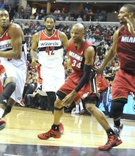 Washington Wizards guard John Wall dribbles past Miami Heat defenders at Verizon Center on Jan.15. Wall scored 25 points as the Wizards upset the defending NBA champion Heat, 114-97.