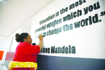 Program Director of City Year Corps, Janae Eason, 27, paints a quote on the wall from Nelson Mandela during a Day of Service in honor of MLK Day at Coolidge Senior High School in Northwest on Monday, Jan. 20.