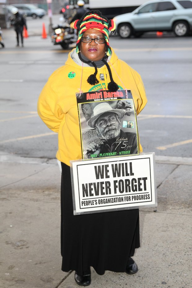An attendee stands with a sign commemorating Baraka.