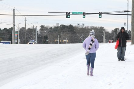 Pedestrians make their way along a desolate Wesley Chapel Road early Wednesday.