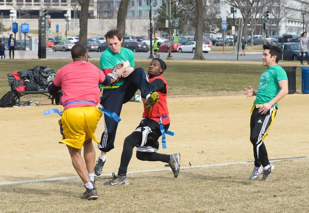 Chad B. catches a pass between two defenders during a flag football game on the National Mall in D.C. on Sunday, Feb. 2. The NAKID Winter Football League plays on the Mall on the weekends.