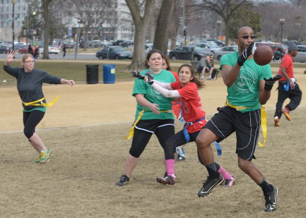 Albert Hailey catches a pass during a flag football game on the National Mall in D.C. on Sunday, Feb. 2. The NAKID Winter Football League plays on the Mall on the weekends.