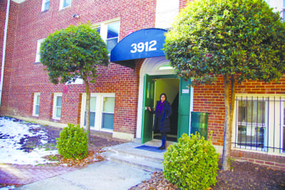 Viviana Ramos, a staff member at Community Lodgings Inc., stands outside one of the organization's rental housing units. The nonprofit, which provides transitional and affordable rental housing, is a partner in Alexandria's Housing Master Plan.