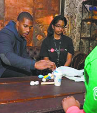 Victor Cruz and Boys & Girls Club students participate in an activity demonstrating how chemistry pertains to protective sporting gear