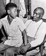 Author and cousin to Emmett Till, Simeon Wright, as a young boy sitting on the lap of his father, Moses Wright in 1955