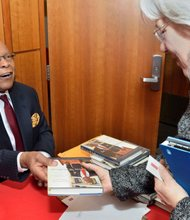 "Former Health & Human Services Secretary Dr. Louis Sullivan signs a copy his new book, ""Breaking Ground: My Life in Medicine,"" at his alma mater Boston University School of Medicine. In the book, Sullivan recounts his extraordinary life beginning with his childhood in Jim Crow Georgia and continuing through his trailblazing endeavors training to become a physician in an almost entirely white environment in the Northeast, founding and then leading the Morehouse School of Medicine in Atlanta, and serving as secretary of Health and Human Services in President George H.W. Bush's administration."