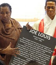 Dr. Joanne Martin, co-founder of the National Great Blacks in Wax Museum with wax figure of boxing champ Joe Louis.