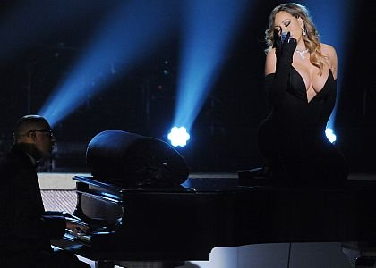"Perched atop a grand piano in a skintight black dress, Mariah Carey debuted her new single, ""Your Mine"" at the ..."