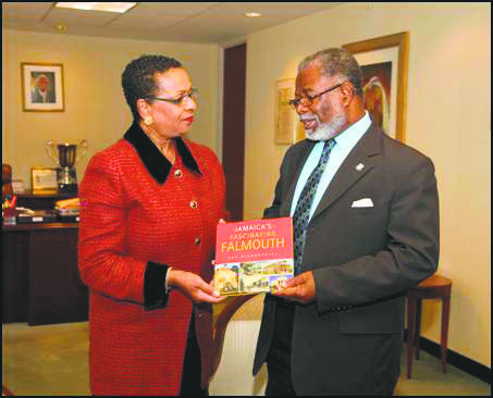 Sandra Scott, Jamaica's deputy director of tourism with responsibility for marketing, presents Consul General Herman G. LaMont with a copy ...