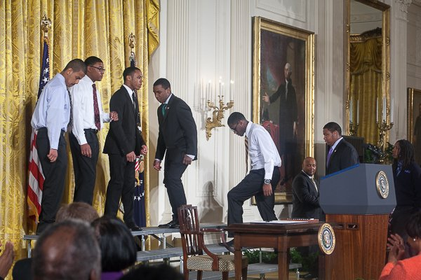"""Members of Becoming a Man (B.A.M.), a program in Chicago, and boys from similar organizations throughout the nation, stand with President Obama in the White House as he rolls out his """"My Brother's Keeper"""" initiative on Thurs., February 27."""