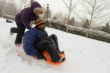 Vance Levy gets a push on his sleigh from his daughter Jahmila, 8, at Meridian Hill Park in Northwest on Monday, March 3.