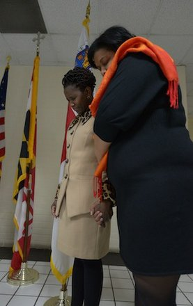 Global Vision Community Health Center founder Toyin Opesanmi (left) and an unidentified woman pray during the grand opening of the health center in Capitol Heights, Md., on Thursday, March 6.