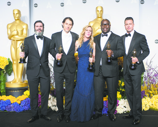 "After winning Best Motion Picture of the Year for ""12 Years a Slave,"" producers Anthony Katagas, Jeremy Kleiner, Dede Gardner, Steve McQueen and Brad Pitt pose backstage with their Oscars."