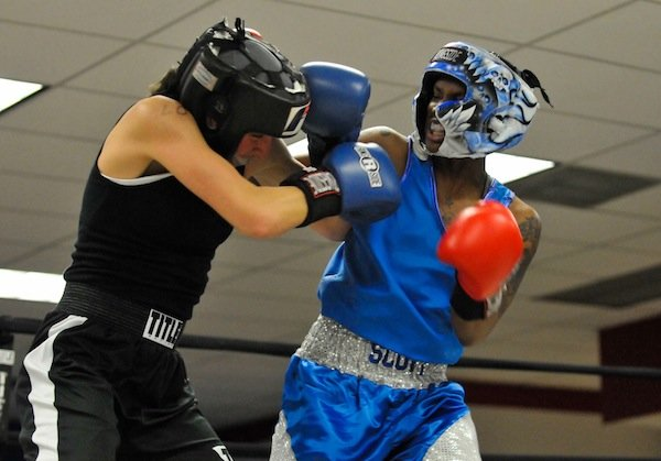 D'Ajah Scott (right) of the Diamonds Ruff Gym lands a punch against Courtney Feldheim during the third week of the 2014 Washington Golden Gloves Championship Tournament on Saturday, March 8, at the Sugar Ray Leonard Boxing Center in Hyattsville, Md.