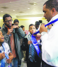Earnest Williams, 11 (bottom left), along with several other young men eager to learn the basics of becoming successful individuals, are shown the proper way to tie a necktie by Brandon Frame, chief visionary officer of the Black Men Can Institute. The Institute held a daylong program at American University in Northwest on Feb. 22.